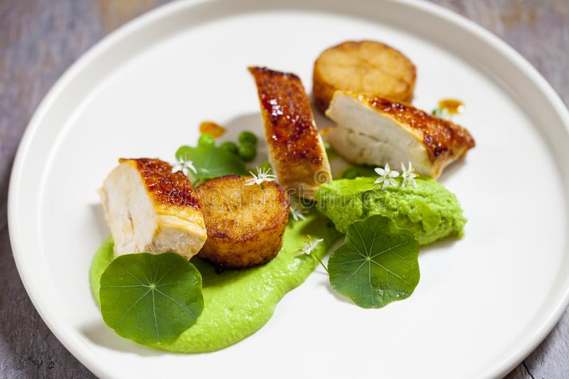 Roast chicken with fondant potatoes, pea mousse, pea puree, garlic flowers and nasturtium leaves stock images