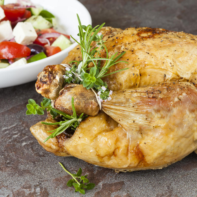 Roast chicken with Fresh Herbs and Greek Salad stock image