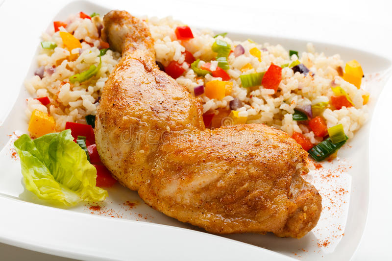 Roast chicken leg. Boiled white rice and vegetables stock photo