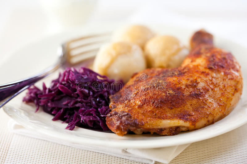 Roast chicken leg with potato dumplings. And red cabbage stock photo