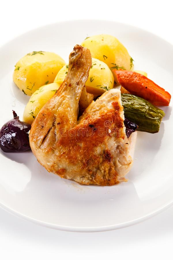Roast chicken leg with potatoes stock images