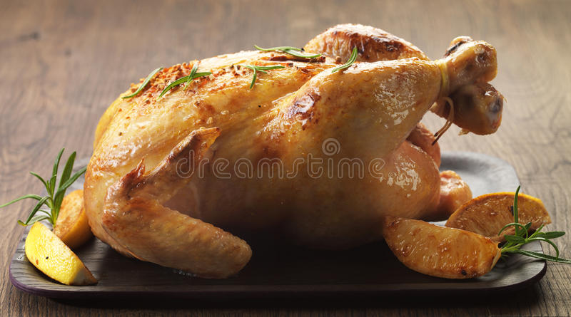 Roast chicken. And lemons on brown wooden plate royalty free stock photo