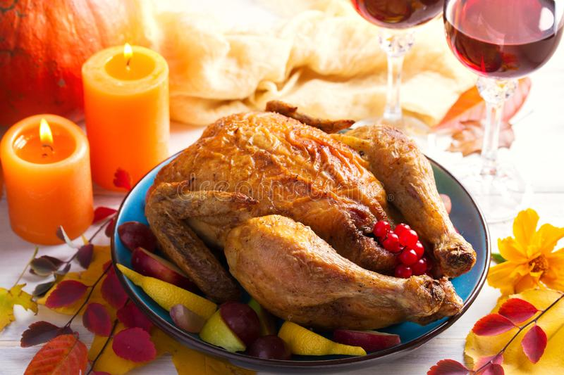 Roast chicken or turkey. Autumn decorations, fruits, pumpkin and berries on the table. Thankgiving dinner. royalty free stock images