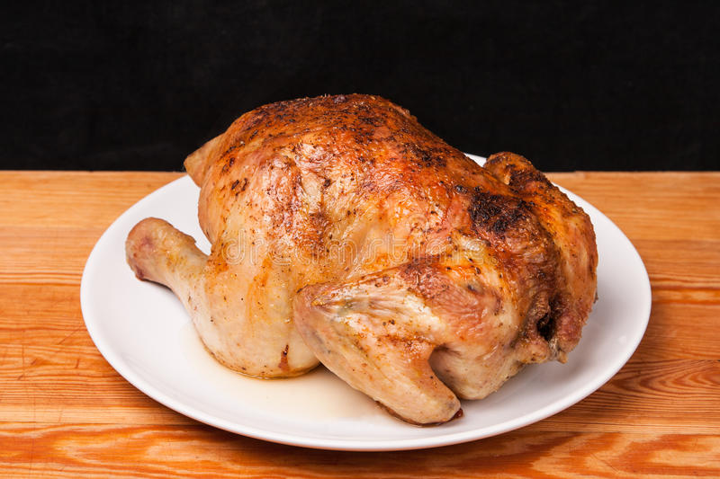 Roast chicken on white plate and wooden royalty free stock photos