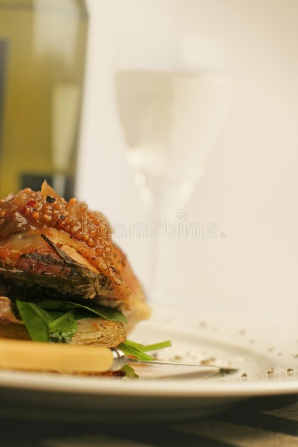 Roast chicken and wine; washout. Roasted lemon chicken over roasted potato and spinach, with mustard fruits. Tall view with wine bottle and glass against strong royalty free stock image