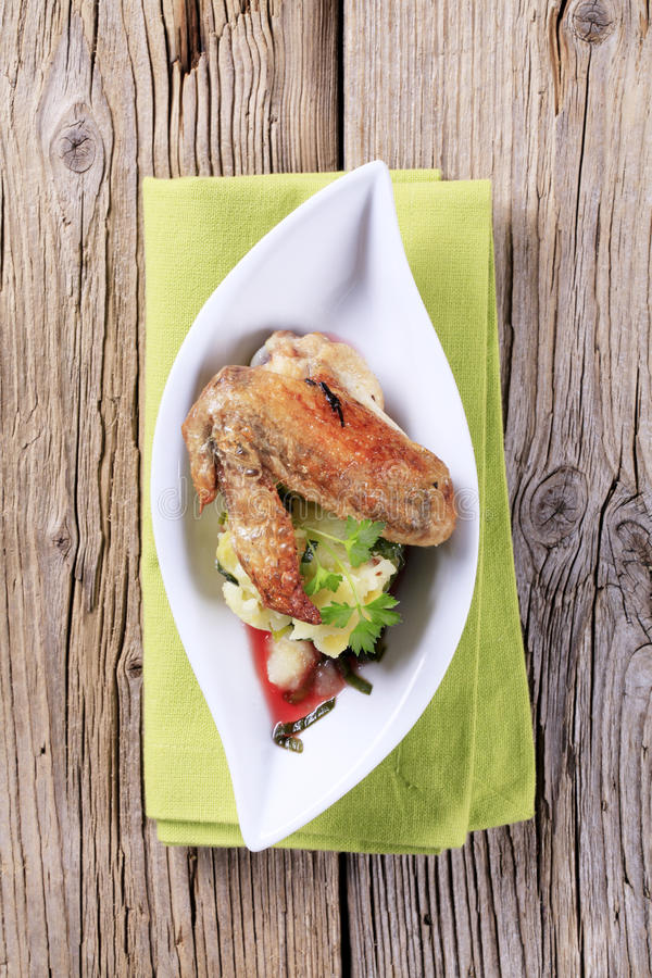 Roast chicken wing with potatoes. Roast chicken wing with crushed potatoes royalty free stock images
