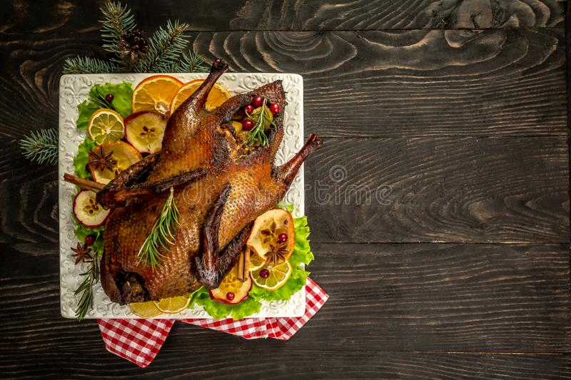 Roast Christmas duck with thyme and apples on rustic wooden table. Thanksgiving or Christmas Dinner. top view. place for text royalty free stock image
