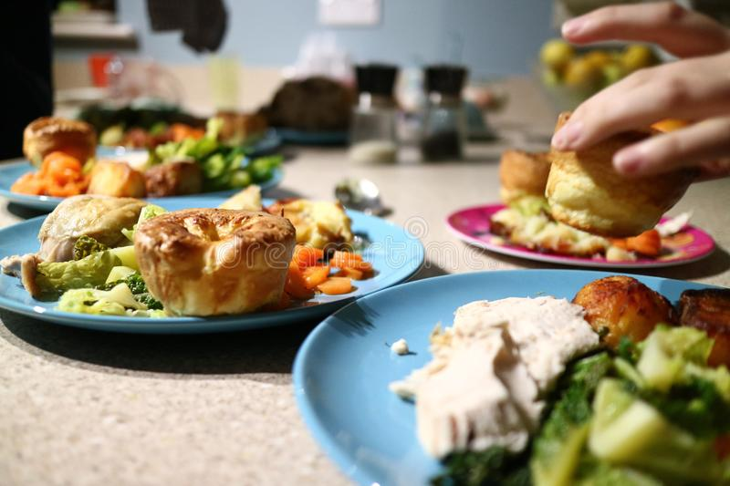 Roast dinners ready to serve while a hand steals a Yorkshire pud royalty free stock photos