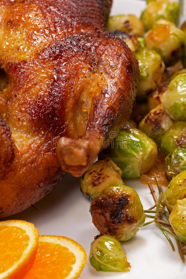 Roast duck. In orange sauce served with brussels sprouts stock photography