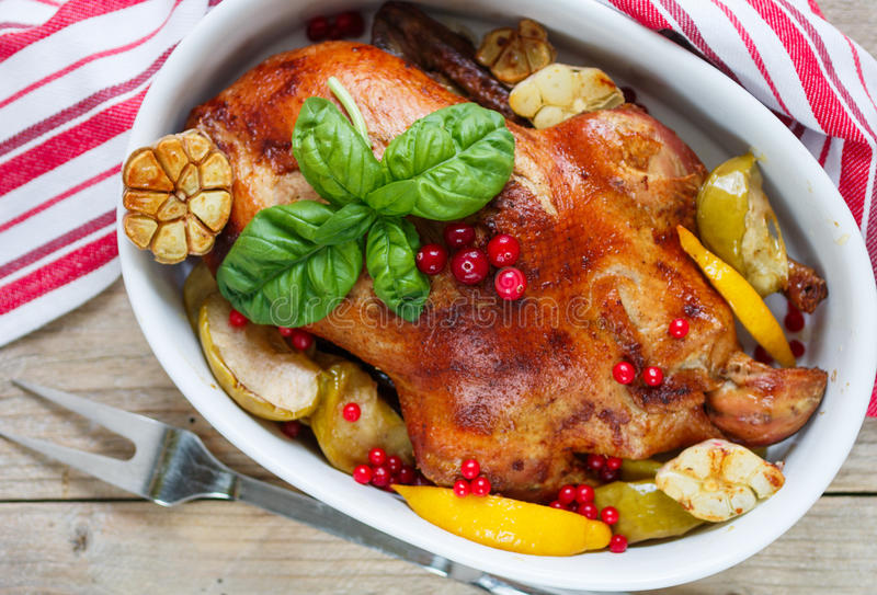 Roast duck with apples, lemon, garlic, cranberries. And spices royalty free stock photo