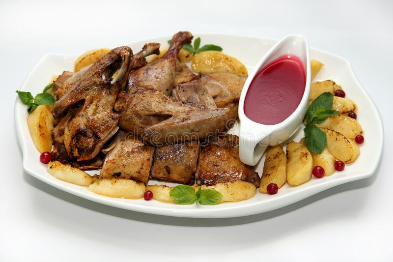 Roast duck with apples. And cranberry sauce stock images
