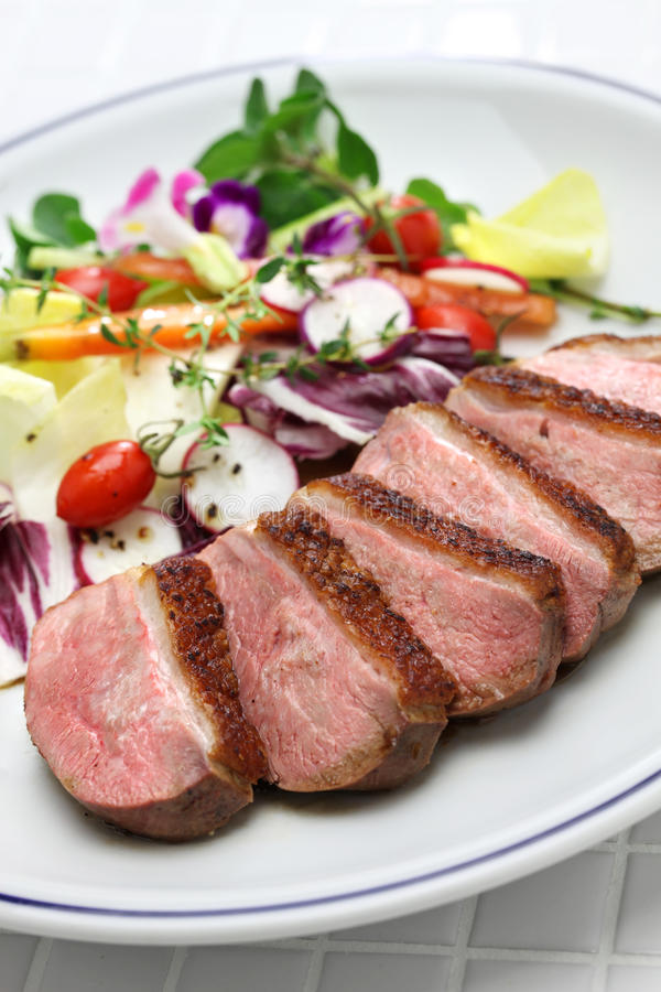 Roast duck breast with vegetables stock image