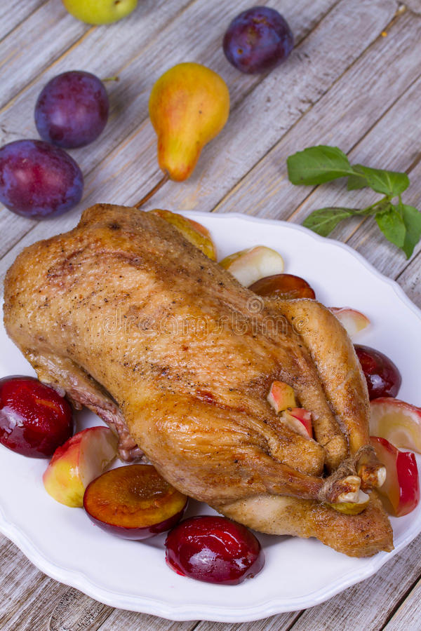 Roast duck with plums and apples. stock image