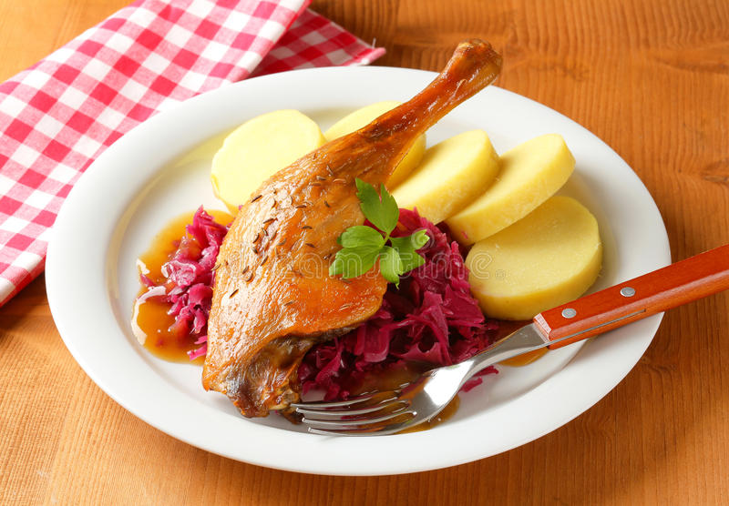 Roast duck with potato dumplings and red cabbage. Dish of roast duck leg with potato dumplings and braised red cabbage royalty free stock images