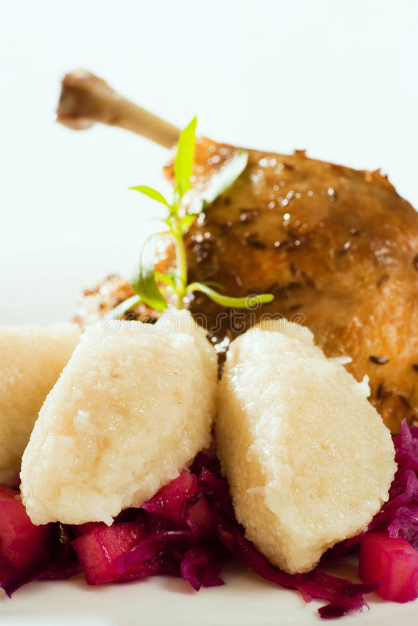 Roast Duck, Red Cabbage and Potato Dumplings. Roast duck and potato dumplings on red cabbage in the foreground stock image