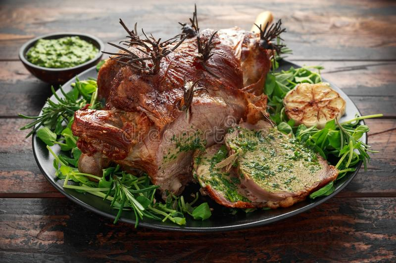 Roast Lamb leg with mint sauce, rosemary and garlic. on black plate, wooden table royalty free stock photo