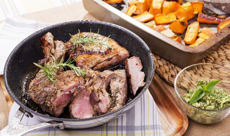 Roast Lamb. Rustic roast lamb with pan juices and rosemary stock photos