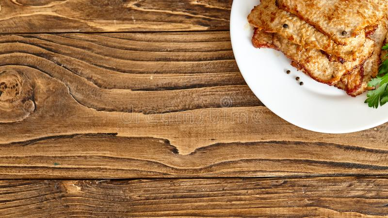 Roast meat in a plate on a wooden table. shot from above. stock photography