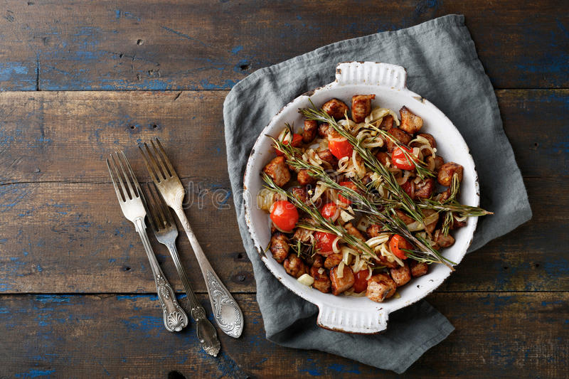 Roast Meat with tomato, onion and rosemary on frying pan royalty free stock photo