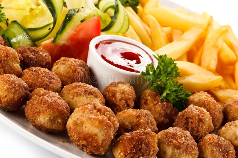 Roast meatballs, French fries and vegetable salad. On white background royalty free stock photos