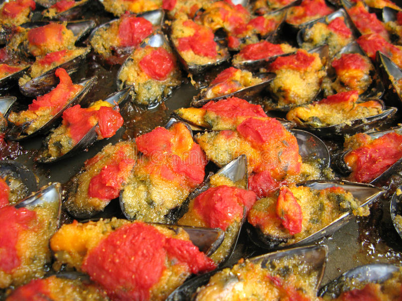 Roast mussels. Seafood preparation with roast mussels and tomato stock photo