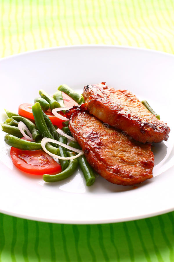 Roast pork. With green beans and tomatoes stock photos