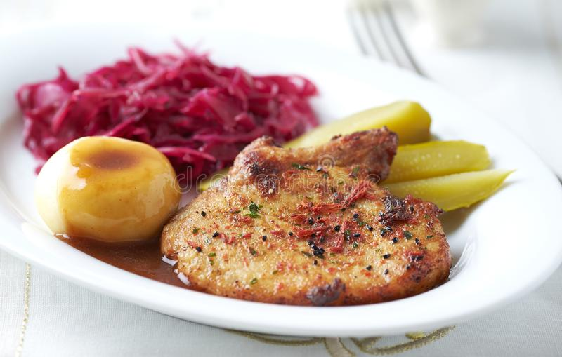 Roast pork chop with potato dumplings and red cabbage royalty free stock images