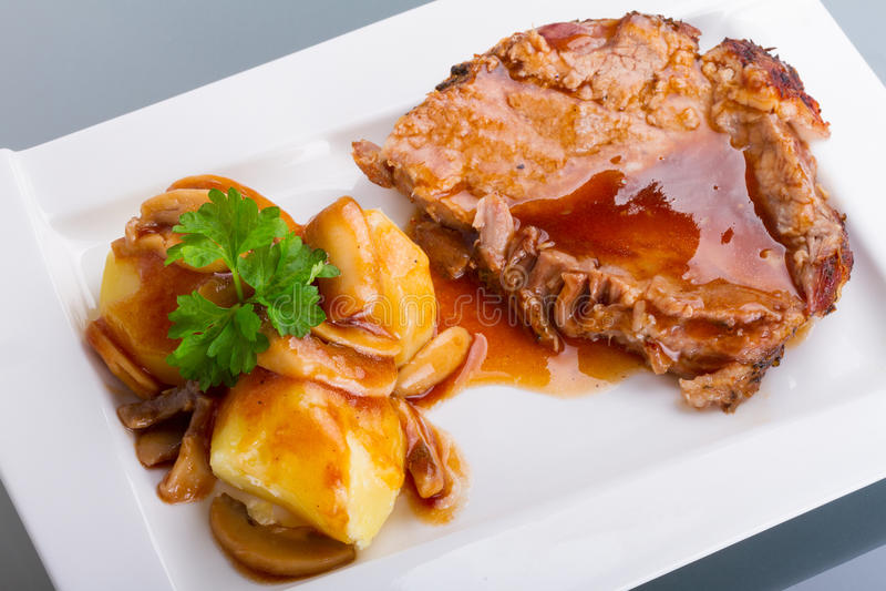 Roast pork with gravy and potatoes stock image
