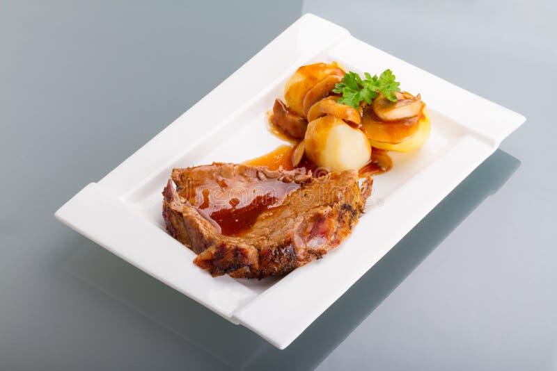 Roast pork with gravy and potatoes royalty free stock photo