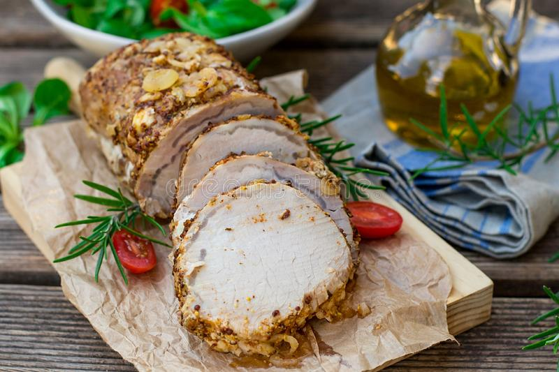 Roast pork loin in mustard marinade with rosemary. Roast pork loin in mustard and onion marinade with rosemary stock image