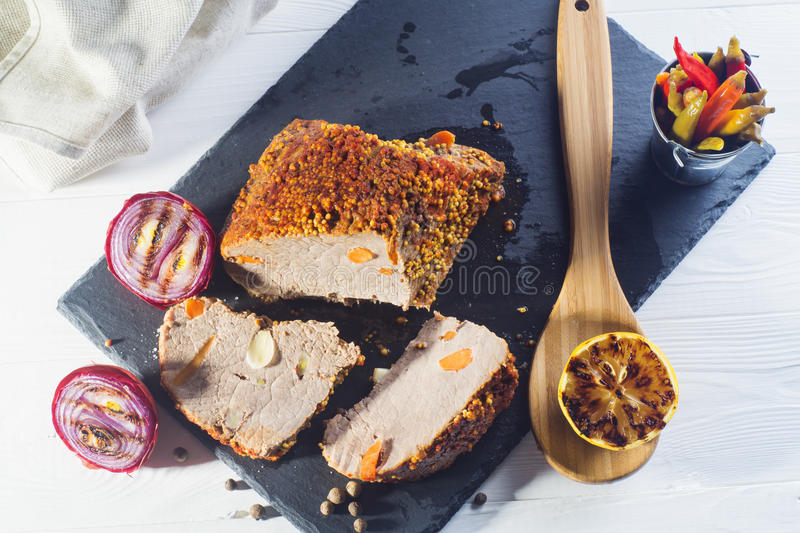 Roast pork with with mustard and lemon. Roast pork with with mustard, onions. pepper and lemon on a white wooden table, top view. Baked meat on a black slate royalty free stock image