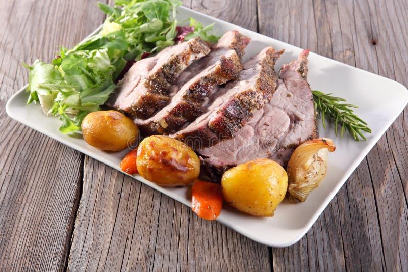 Roast pork neck. On rustical background royalty free stock image