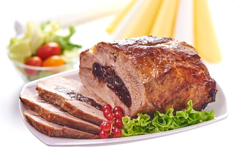 Roast pork with prunes on blurred background, close-up.  stock photography
