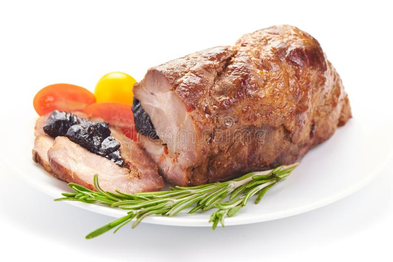Roast pork with prunes, isolated on white background royalty free stock images