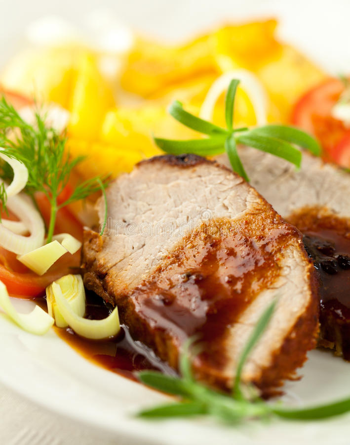 Roast pork with sauce and herbs royalty free stock photos