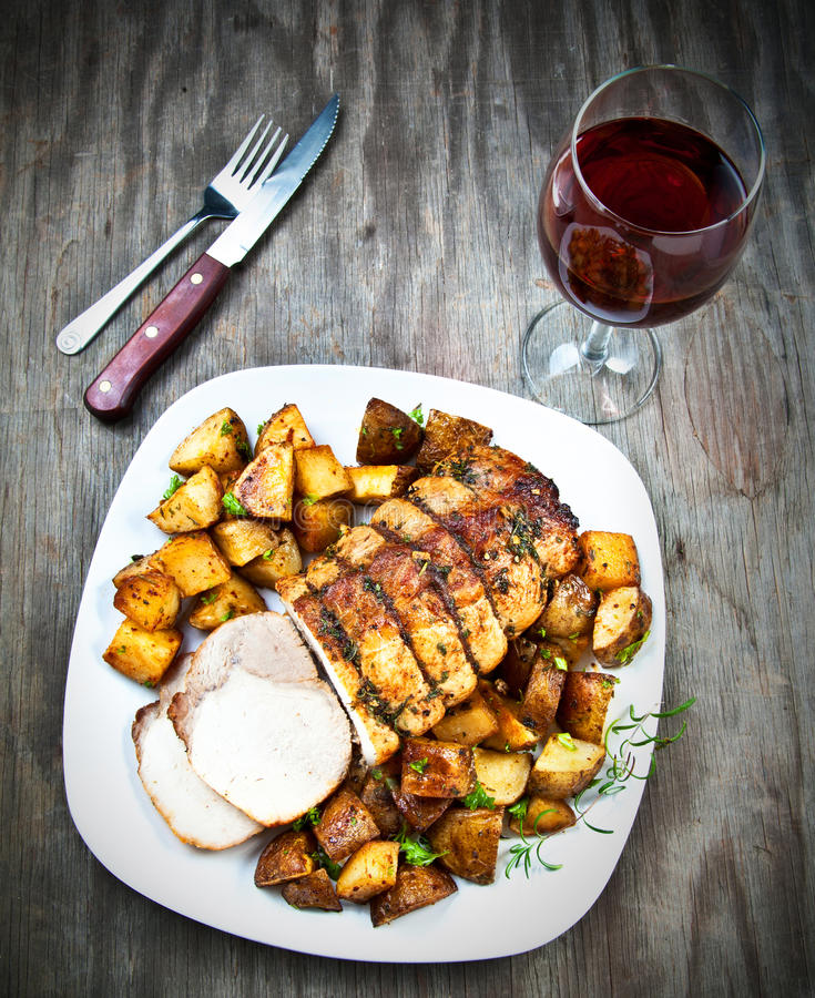 Roast pork, sliced. With potatoes and a glass of wine on old wood royalty free stock photos