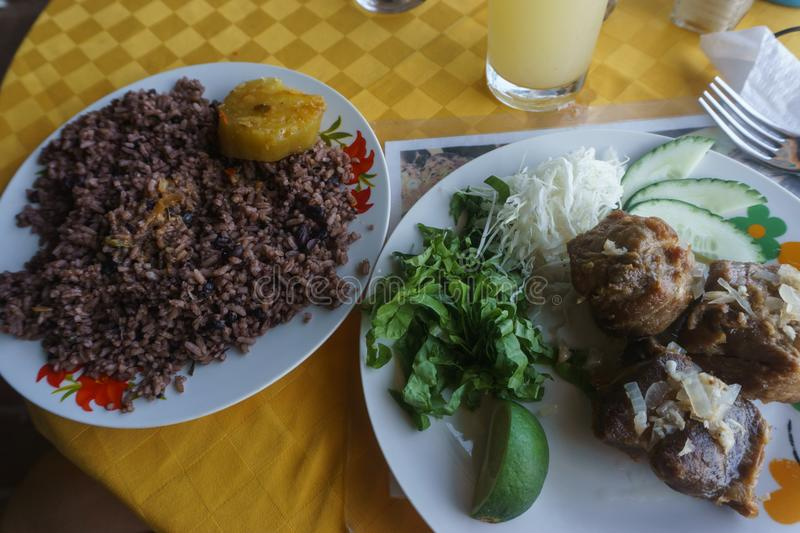 Congri, Rice with beans and meat, a typical dish of Cuban food. Roast pork, typical vat food with salad and lemon served on a white plate stock photography