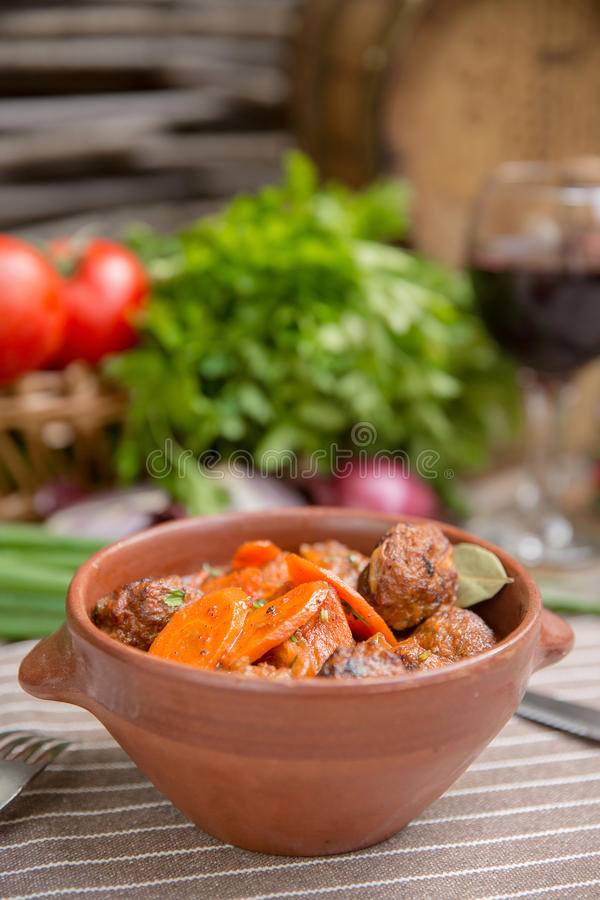 Roast in a pot with beef and vegetables. Roast in a pot with beef and carrots rustic dish royalty free stock photography