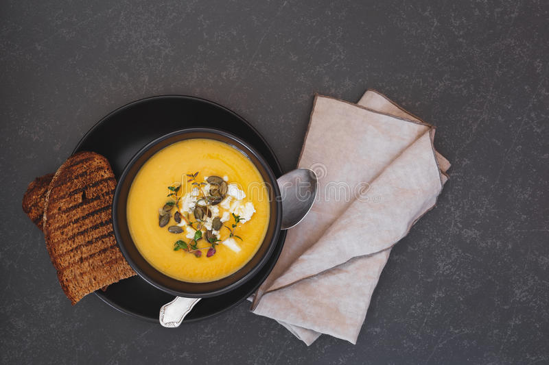 Roast pumpkin soup with pumpkin seeds in bowl on rustic table stock photo