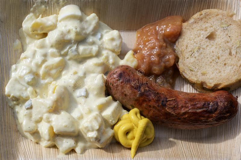 Roast sausage with potato salad, mustard and bread on a bamboo plate, fast food to go on a street festival, top view from above. Roast sausage with potato salad stock photos