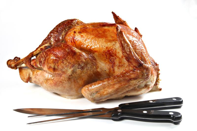 Roast turkey with carving fork and knife, isolated on white back royalty free stock photo