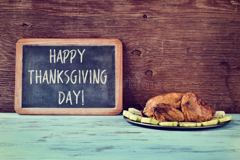Roast turkey and chalkboard with the text happy thanksgiving day stock photography