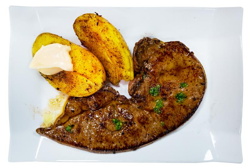 Roast veal liver with potatoes on a white plate royalty free stock image