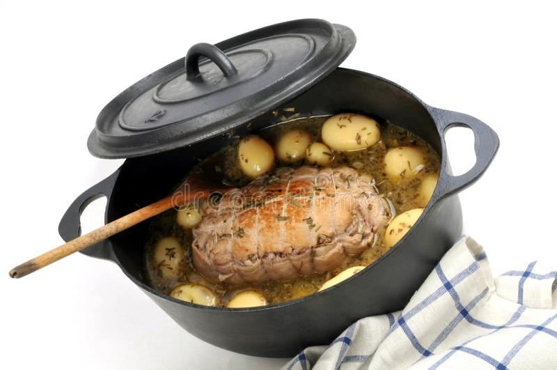 Roast veal with potatoes in sauce in a cast iron casserole on white background stock image