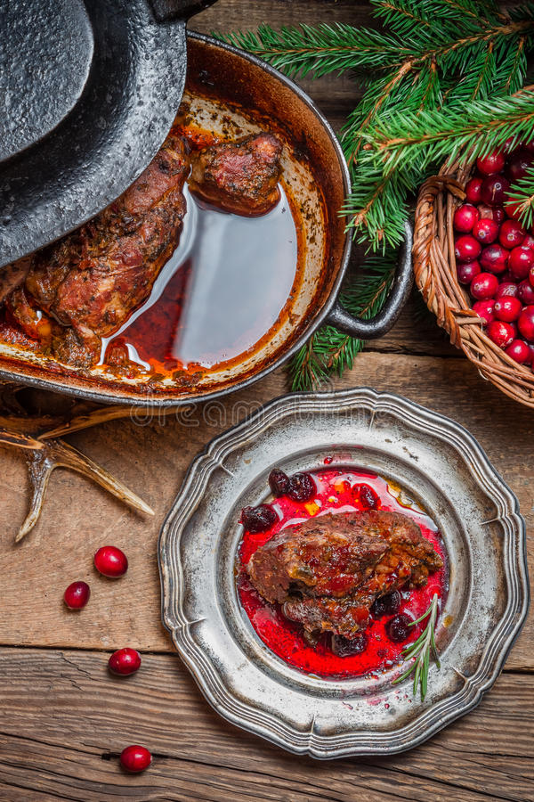 Roast venison with cranberry sauce and served in the forester lo royalty free stock image