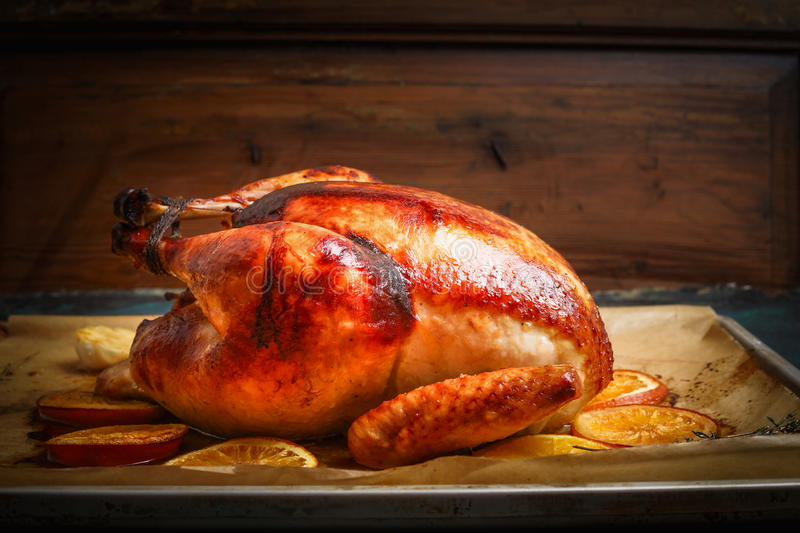 Roast whole turkey or chicken over wooden background. Side view royalty free stock images