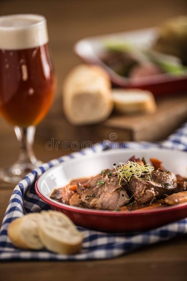 Roast wild boar with carrot mushrooms, baguette and draft beer.  stock images