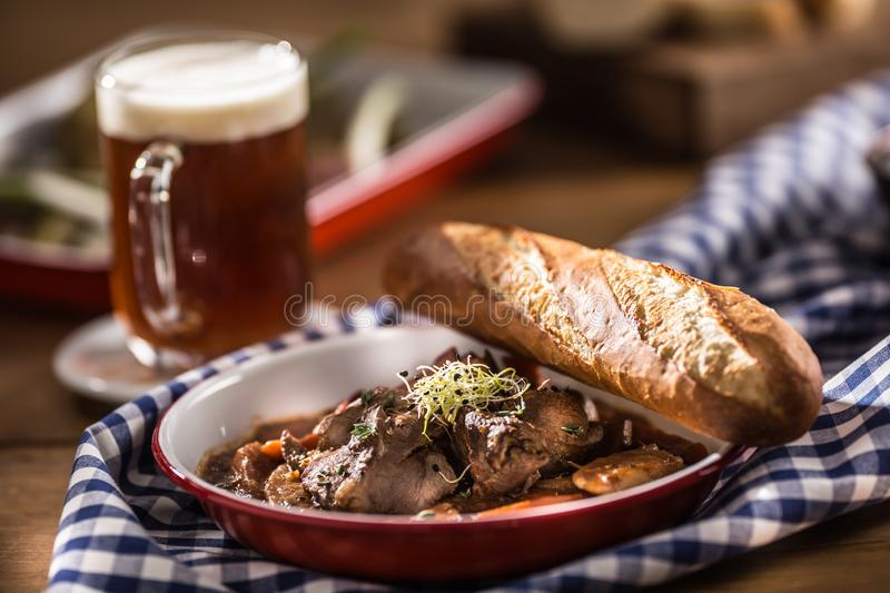 Roast wild boar with carrot mushrooms, baguette and draft beer.  stock photography