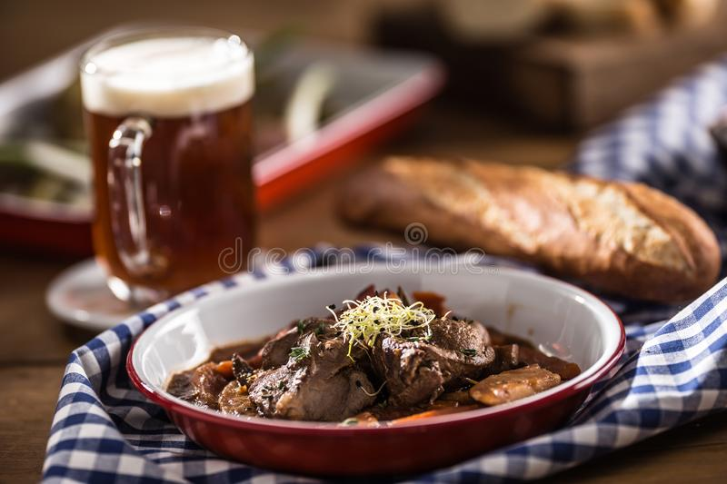 Roast wild boar with carrot mushrooms, baguette and draft beer.  royalty free stock photography