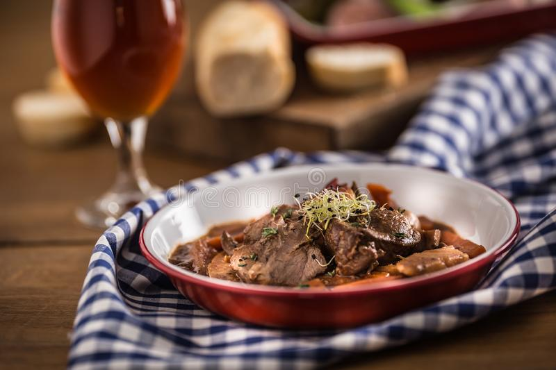 Roast wild boar with carrot mushrooms, baguette and draft beer.  royalty free stock images